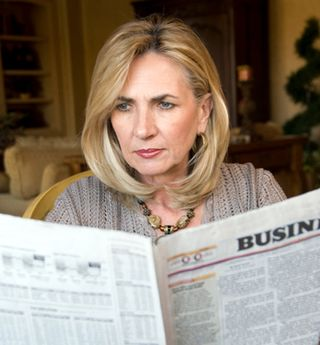 Boomer woman reading newspaper